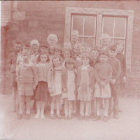 Mrs Simpson Headteacher of Mossdale School 1950's taken with the children (unidentified)