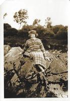 Smiling woman sitting on rocks
